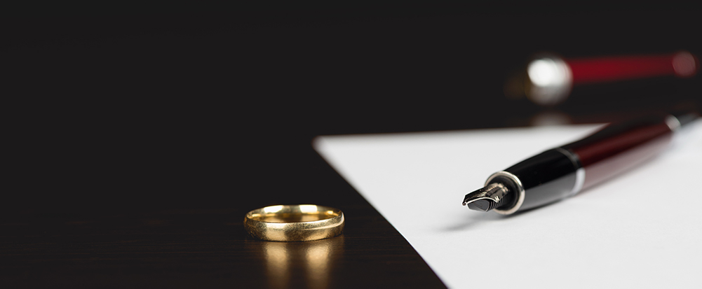 wedding ring off to the side of divorce paperwork